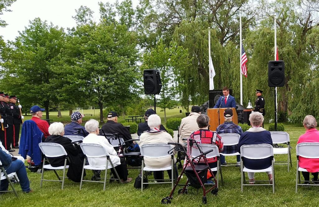 Group of seated veterans look to the male speaker in front of them in the park, speaking from the podium with the Veteran's War Memorial behind him.