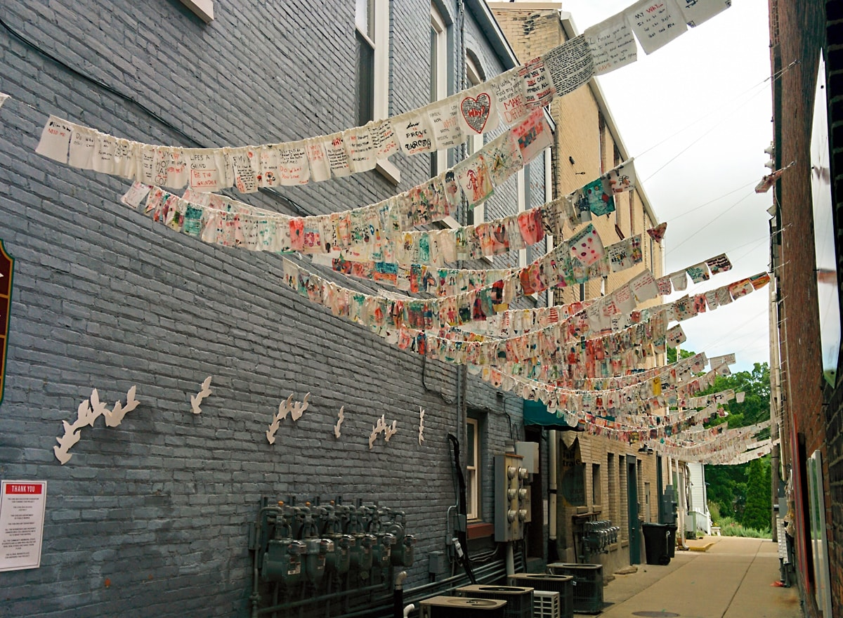 lines of brightly colored flags flutter in the breeze between two brick buildings