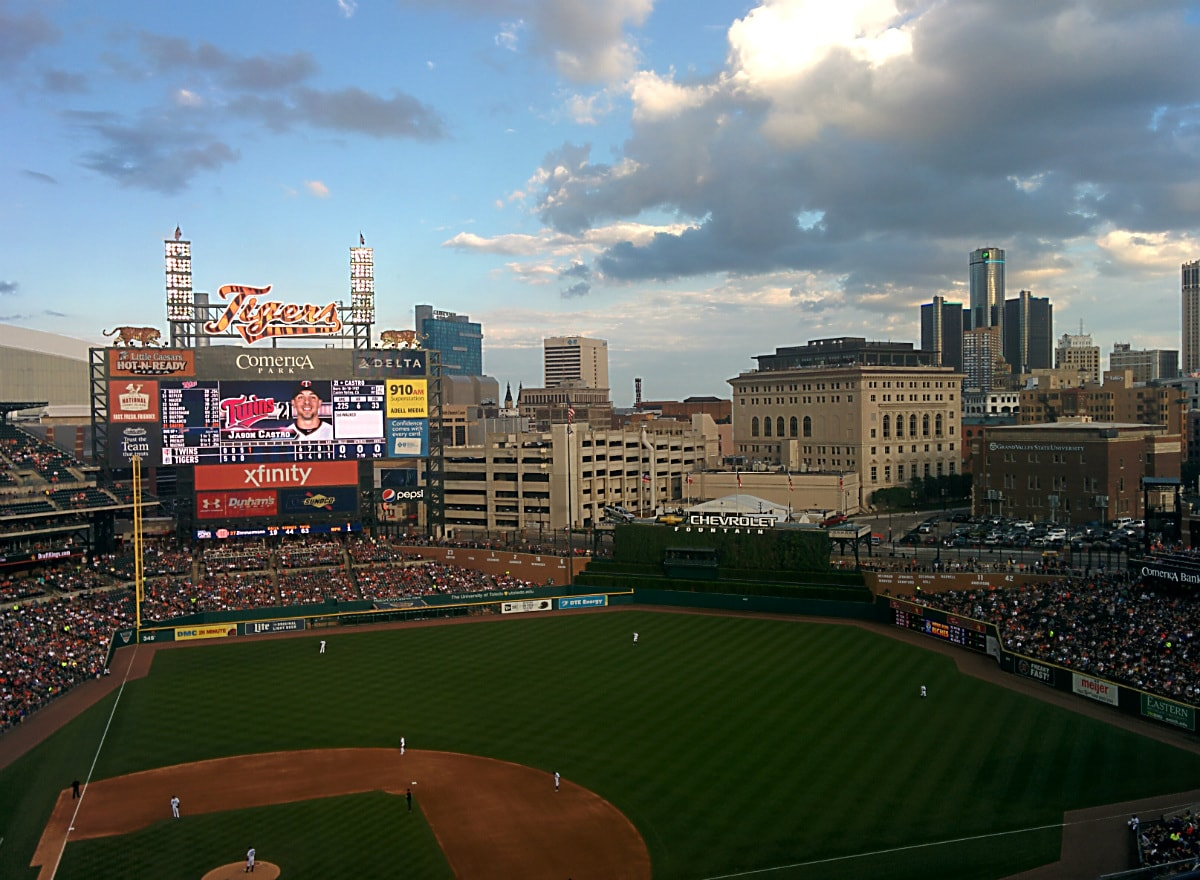 Baseball field with fans filling the stands at Comerica Park, gray clouds in a blue sky