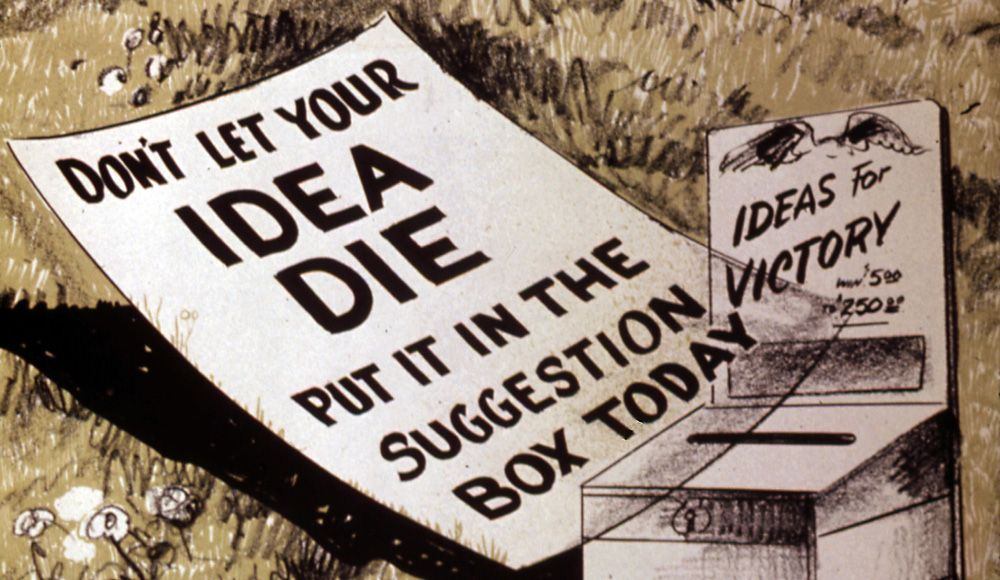 An Ideas for Victory suggestion box with a printed message laying next to it with the sentences, Don't let your idea die. Put it in the suggestion box today.