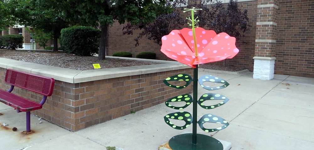 Dotty, a pink and white polka-dot with green leaves painted steel sculpture