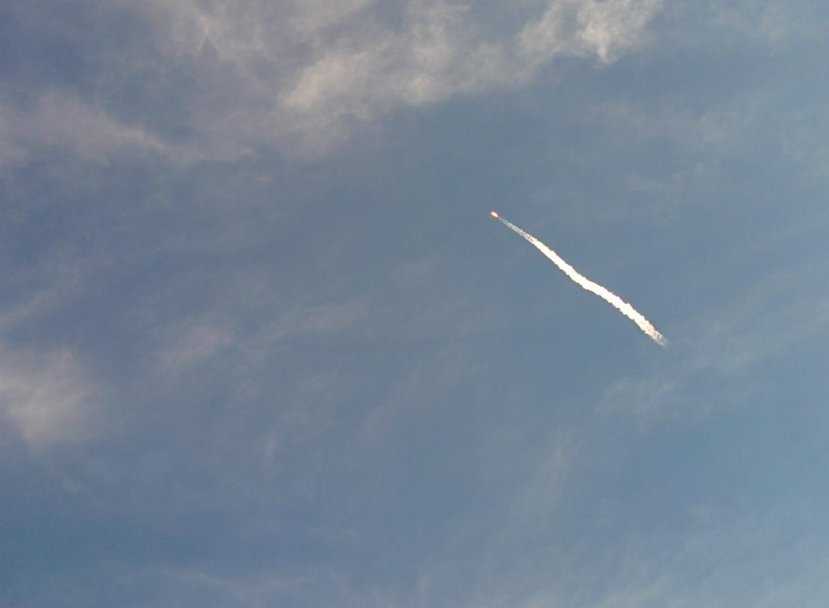 Falcon rocket entrails seen across the blue sky.