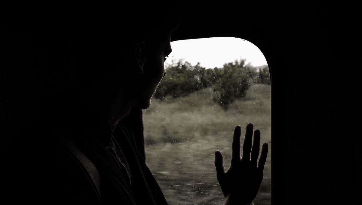 man sitting in train waves through the window