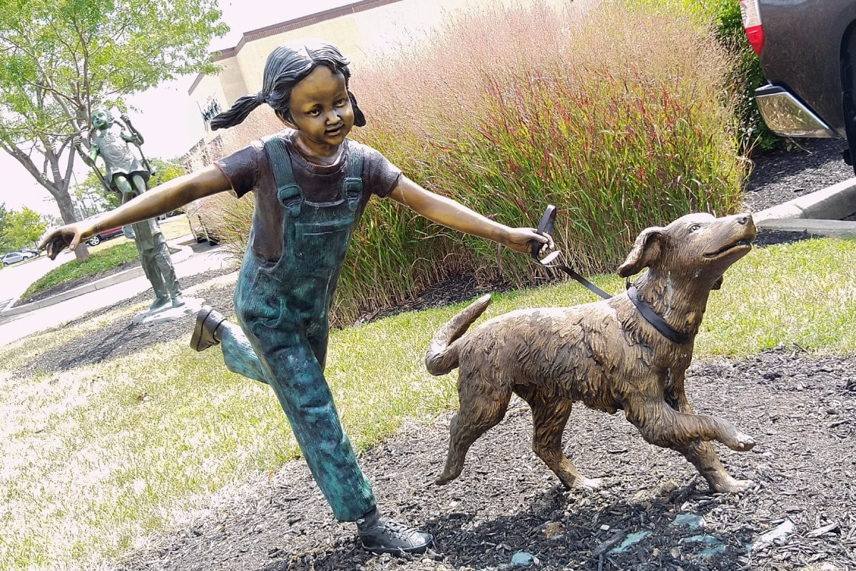 young girl holds on to the leash of her dog as she gleefully runs.