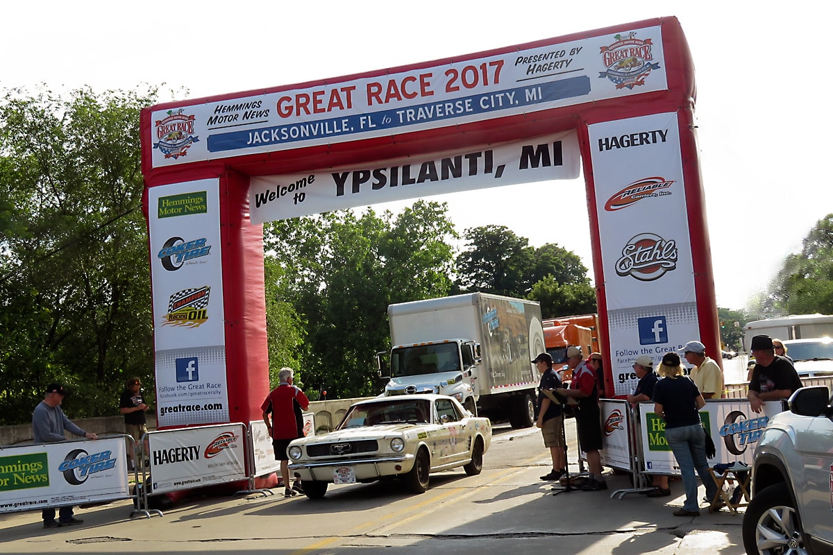 white Ford Mustang arrives in Depot Town, under the red and white Great Race archway