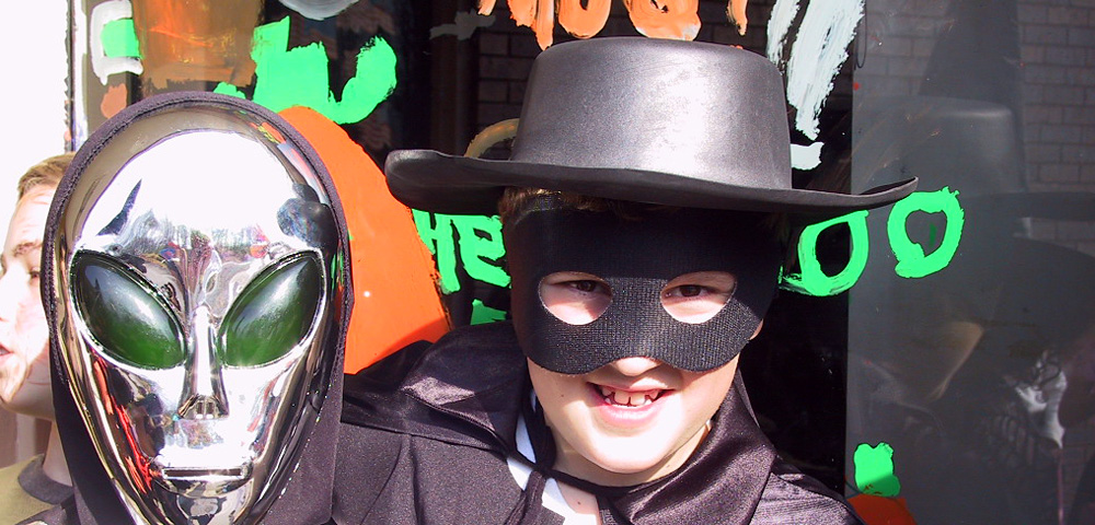 Two children in Halloween costumes, one a visitor from outer space, the second as Zorro