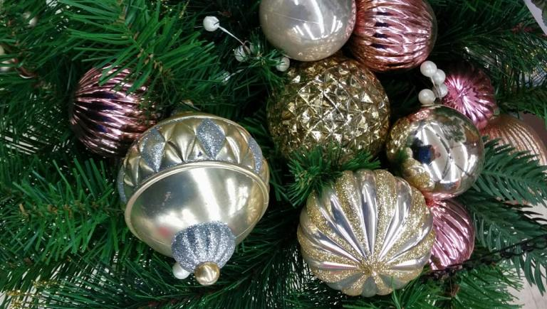 silver and gold metallic ornaments hang on an evergreen branch.
