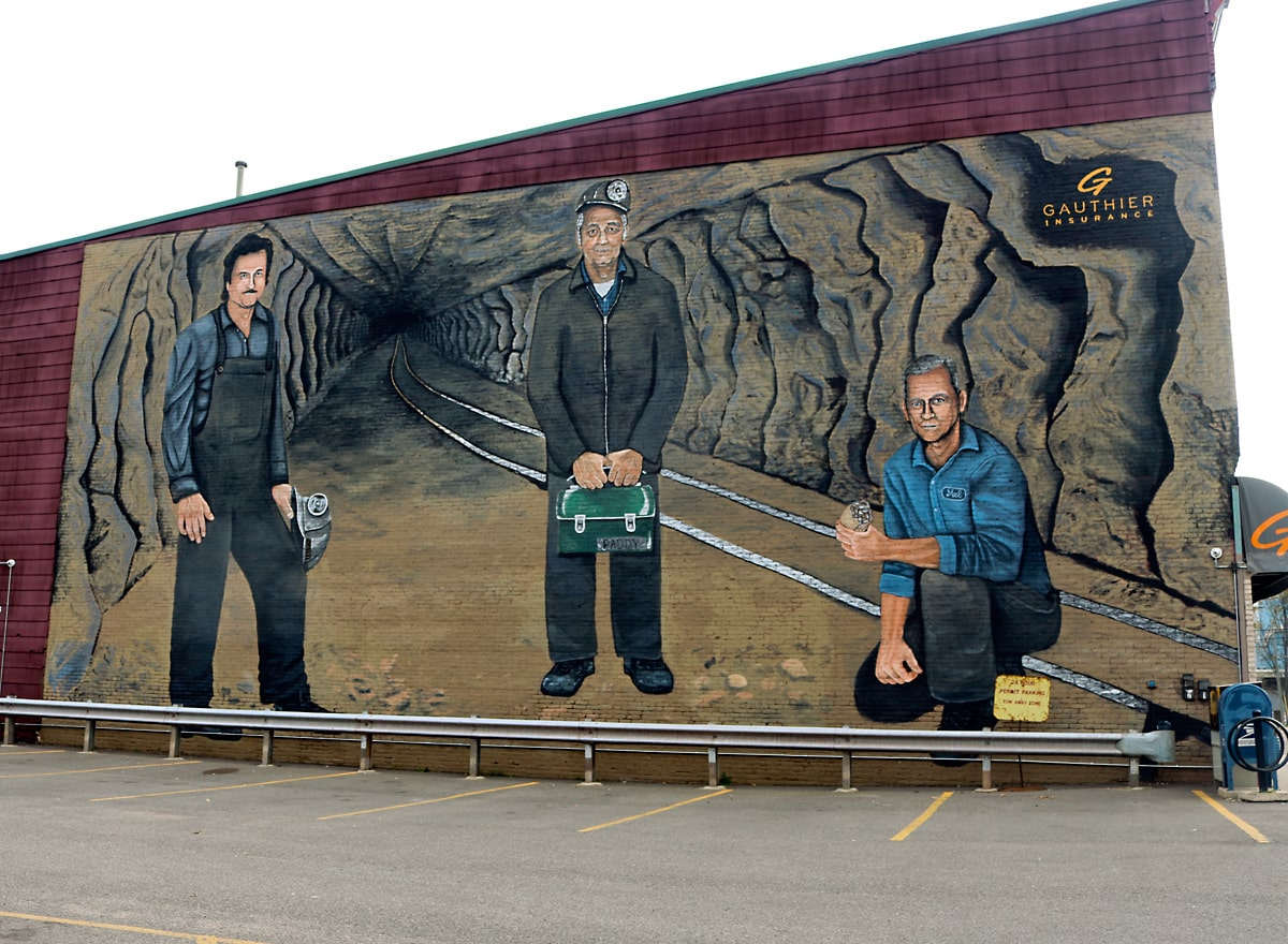 mural three iron ore miners, two standing, one kneeling, inside iron ore mine.