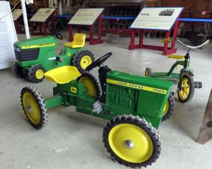 Green John Deere child-sized tractor, tricycle, and lawn mower
