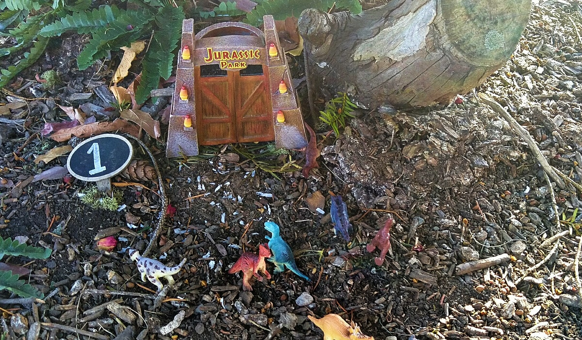 Brown fairy door labeled Jurassic Park is surrounded by colorful miniature dinosaurs on the wood mulch ground.