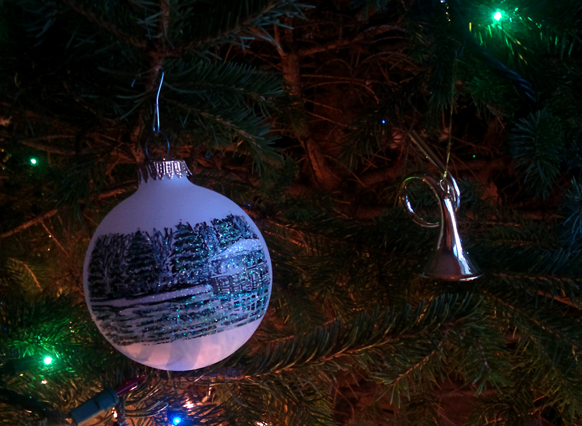 Kitch-iti-kipi spring on a white globe ornament next to brass French horn ornament hanging on Christmas tree.