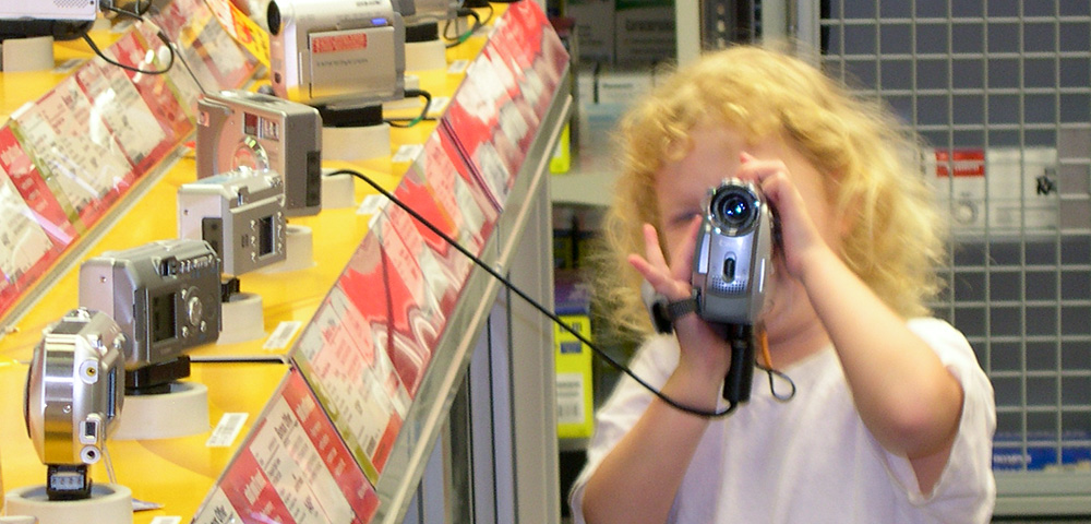 Little girl holding camcorder in camera aisle at store