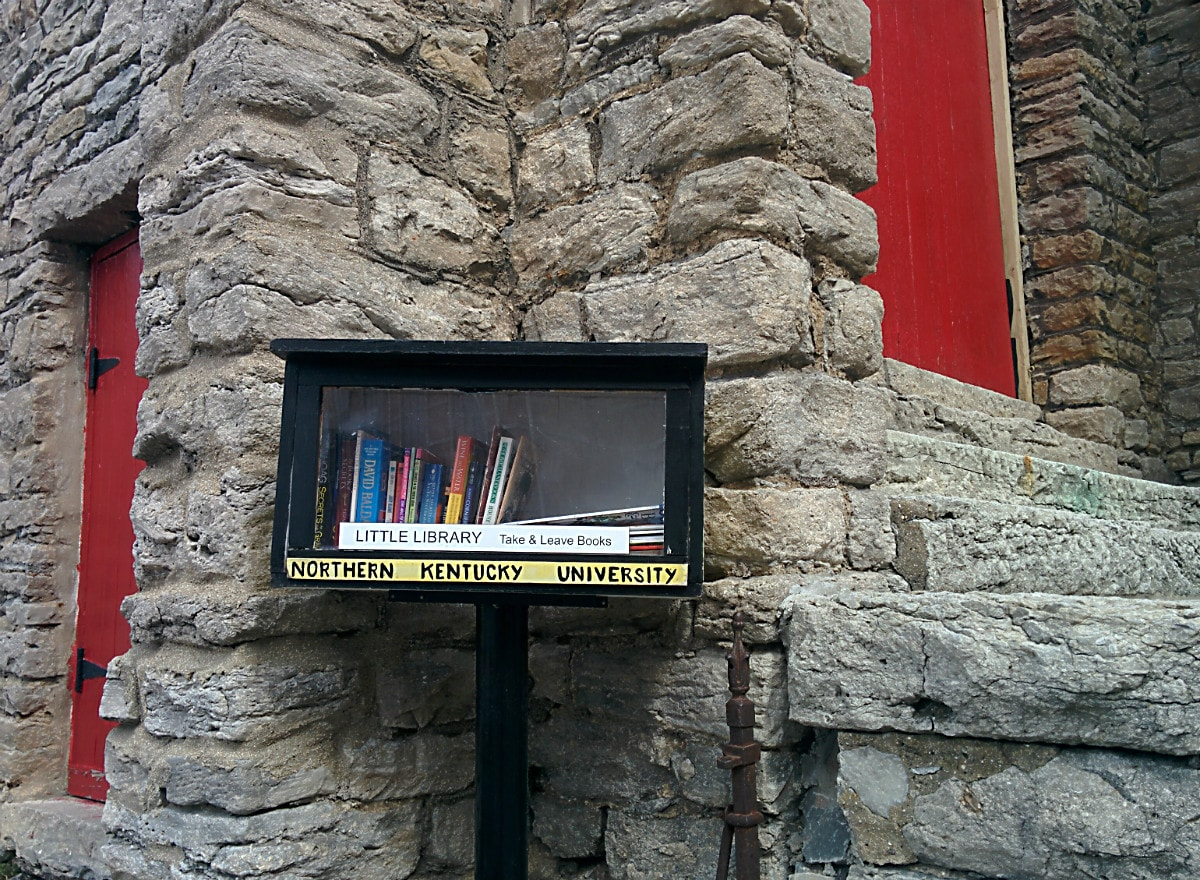 Little Library box with the gray concrete blocks and red doors of the church in the background