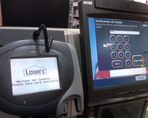 Lowe's self-checkout with English displaying in card reader while touchscreen displays Spanish