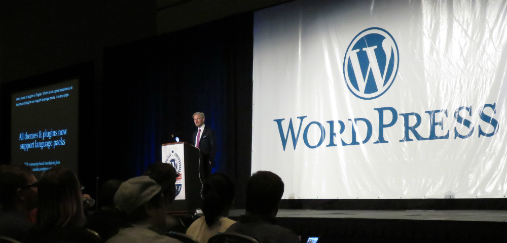 Matt Mullenweg at podium in dark conference room, WordPress banner behind him.