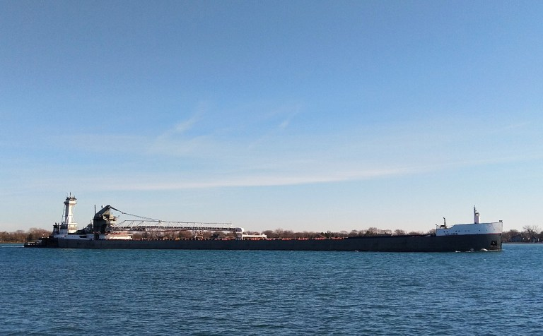 Long freighter travels downbound in the blue waters of the Detroit River.