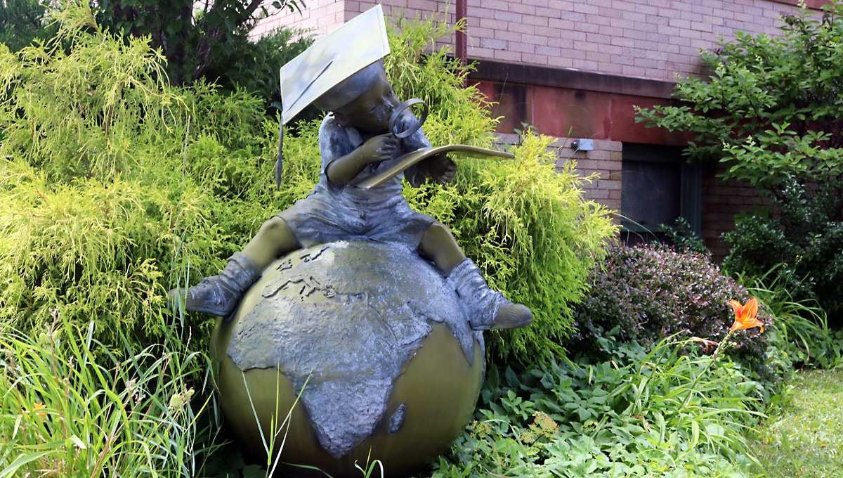 sculpture of child with graduation cap sits on a large globe as he explores a map in an atlas