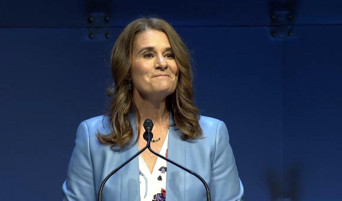 Melinda Gates at lectern, pausing and smiling during her talk