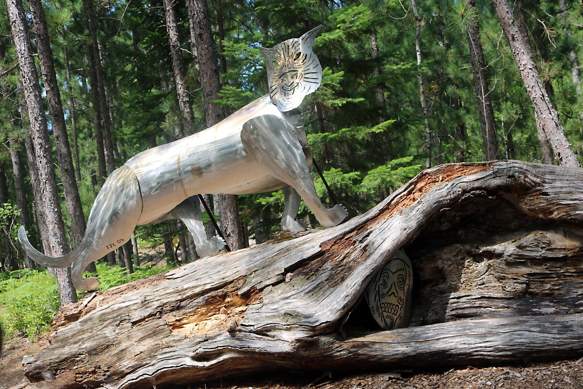 silver metal lion poses on a log as a metallic face sculpture peers out from a cavity in the log