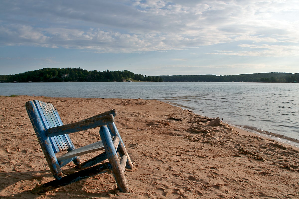 blue wooden chair on golden brown beach overlooking clear blue waters of Walloon Lake in northern Michigan.