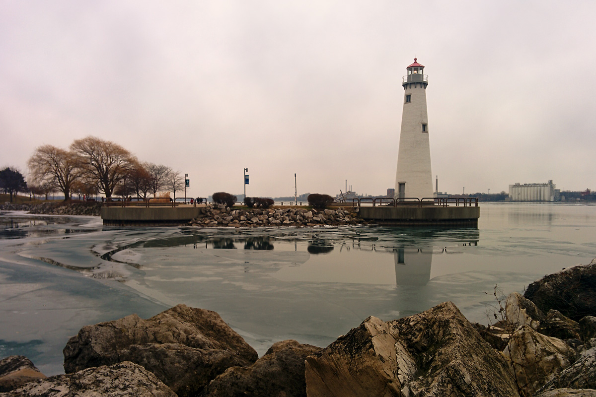 The lighthouse of the Milliken State Park on a cloudy day, ice covers the harbor of the state park