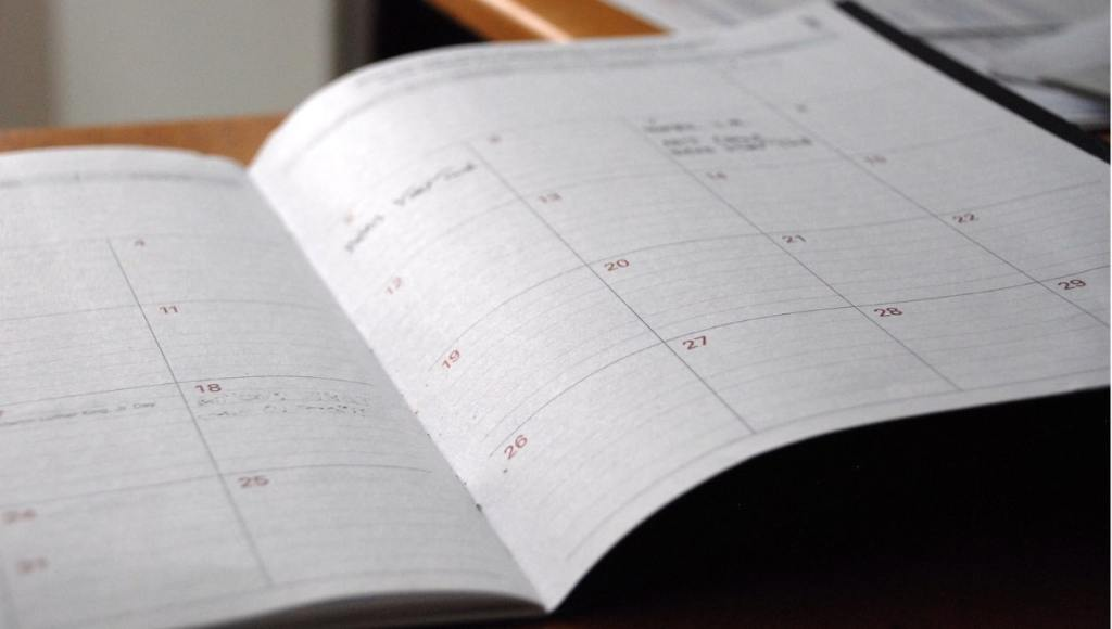 open paper monthly planner with days organized in rows and columns.