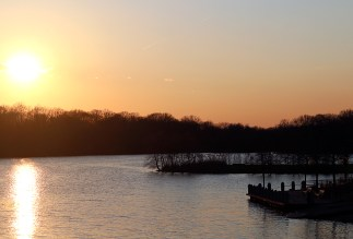 Sunset over Newburg Lake, showing trees in the background and Newburgh Comfort Station