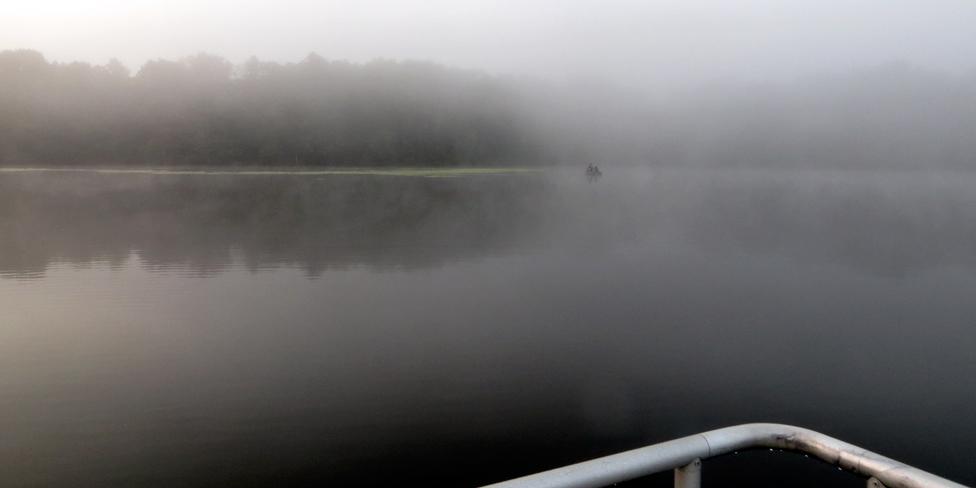 Barely seen fisherman as dense fog covers Newburgh Lake