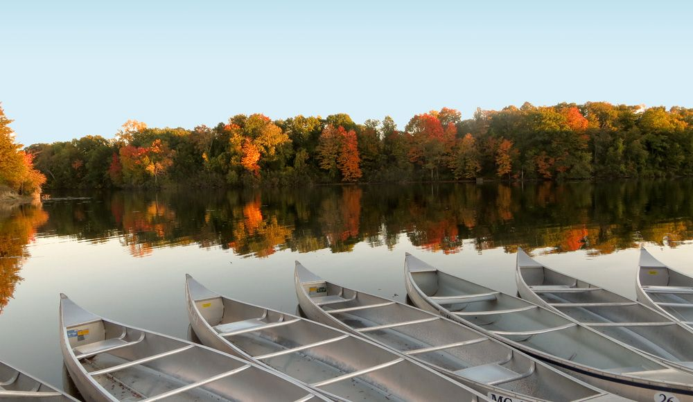 Canoes along Newburgh Pointe lakeshore give way to the reflection of red and gold colors of the trees on the opposite shore