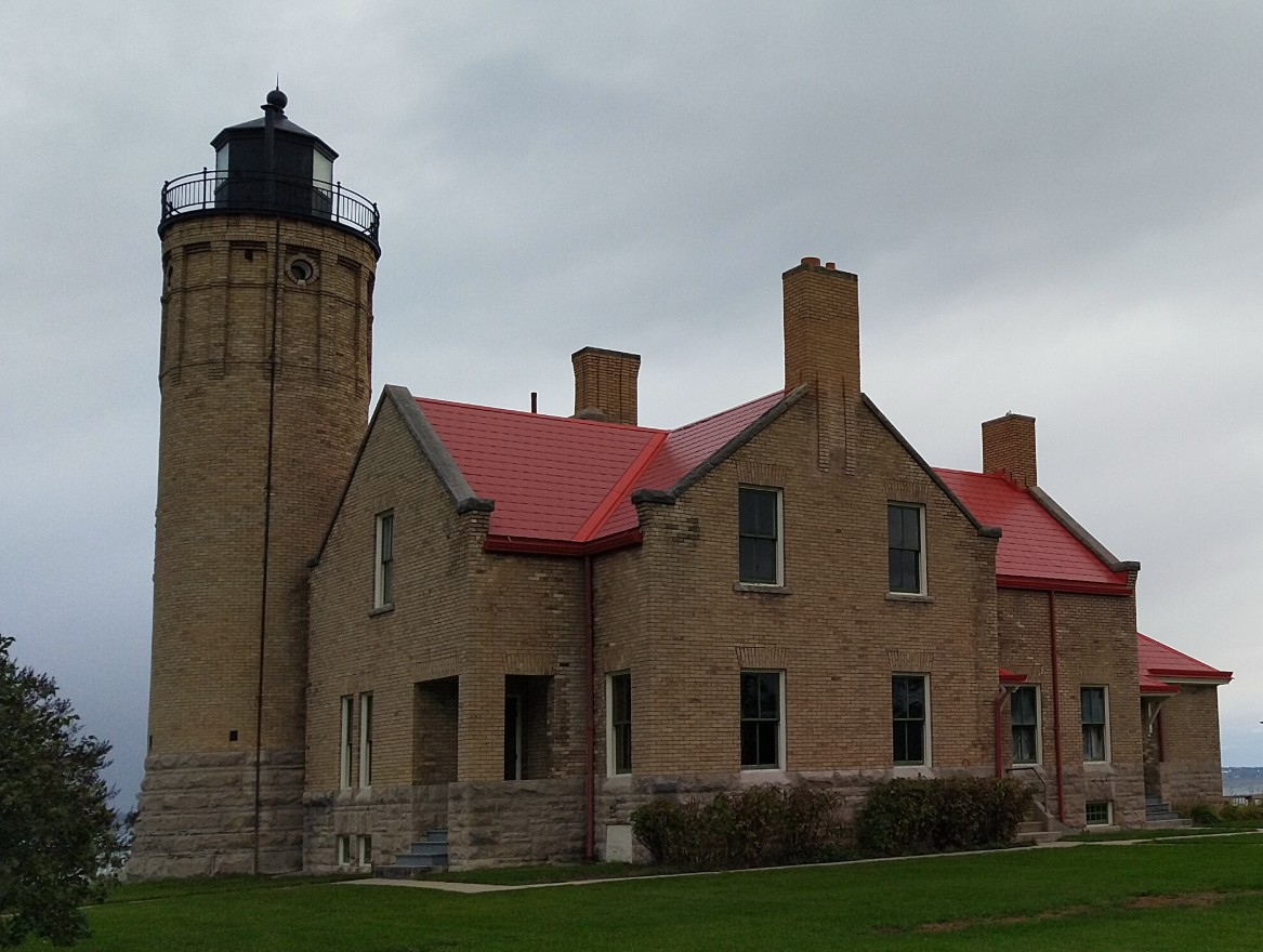 light brown brick lighthouse with red roof with castle-like architecture, with Straits of Mackinac in the background.