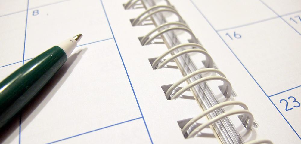spiral-bound desk calendar showing days of the week
