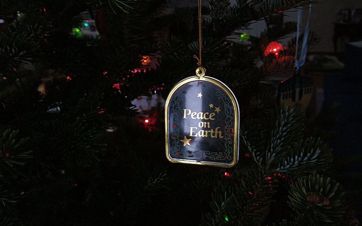 Hanging from the Christmas tree, colored lights light up the gold-trimmed flat glass ornament etched with the words Peace on Earth.