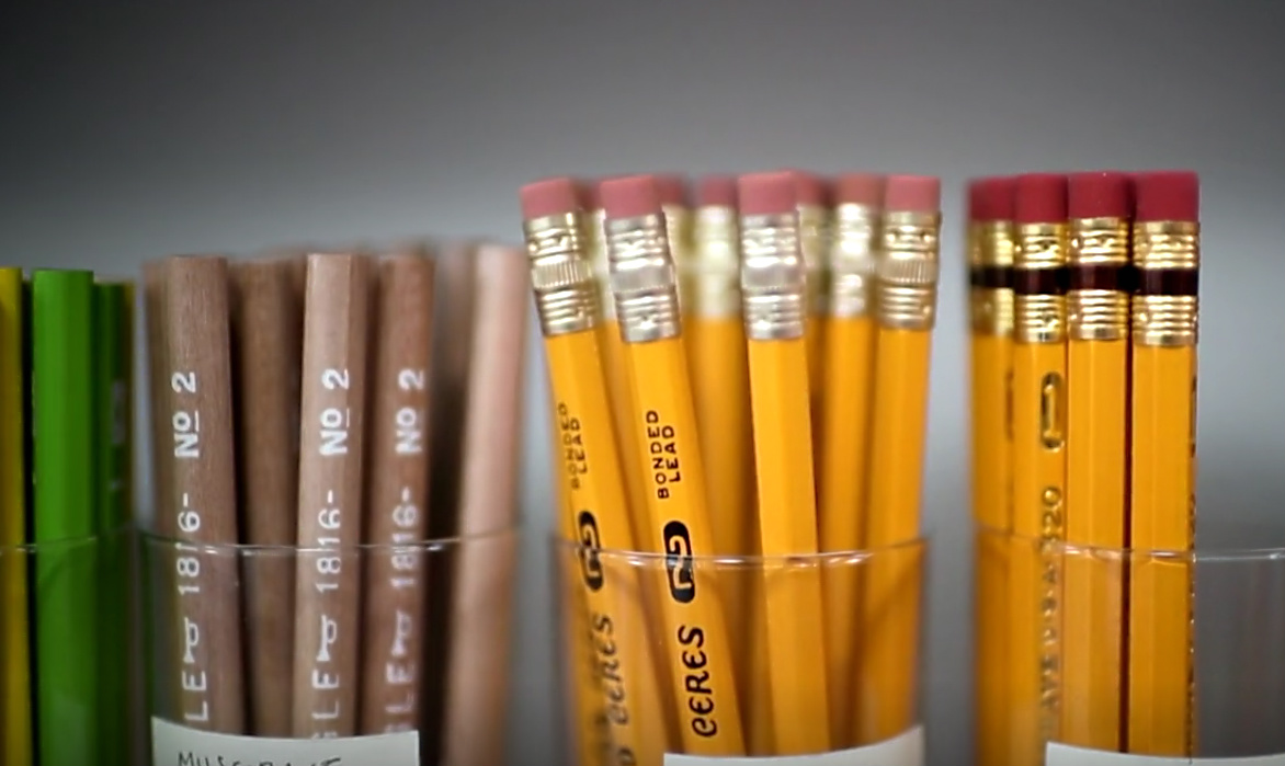 cups of brown and yellow eraser-topped pencils