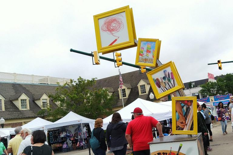Four yellow-framed pictures rise from a cart in a graceful arch, welcoming everyone to the art fair in downtown Plymouth streets lined with white-tent booths and people.