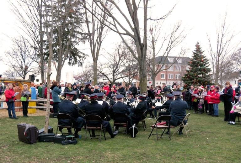Families and friends gather in Kellogg Park around Salvation Army Band, singing Christmas carols