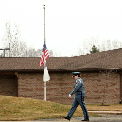 Flag flying at half-mast as police officer walks past