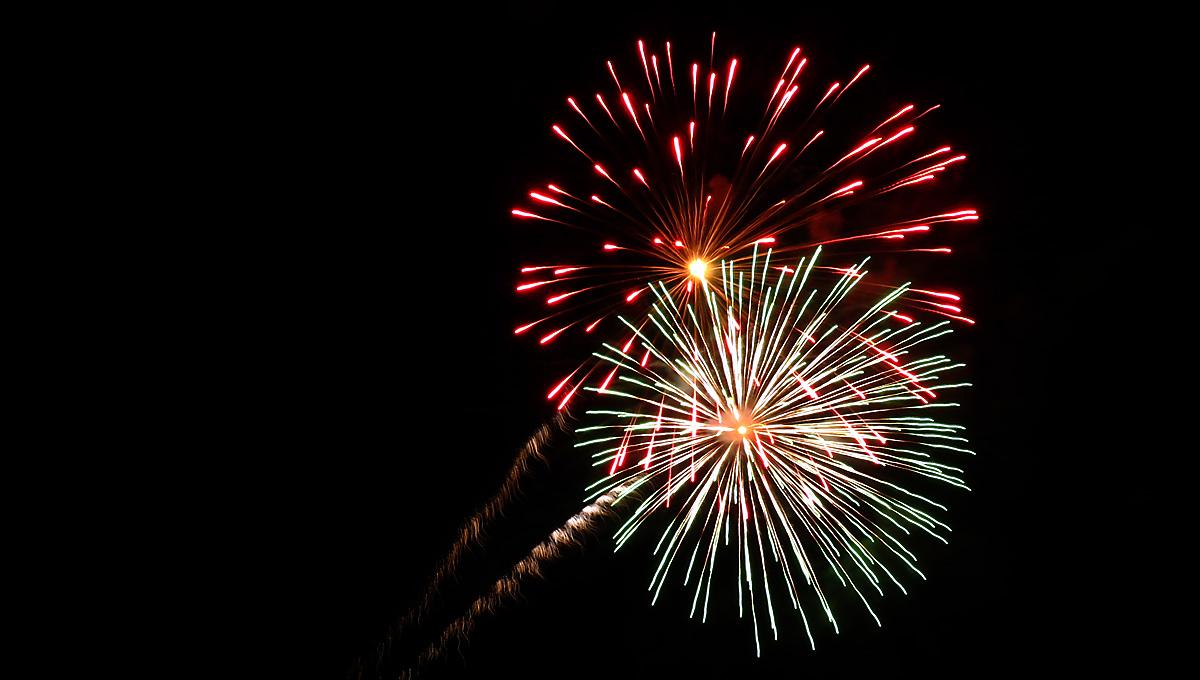 red and white sunburst fireworks against a dark sky