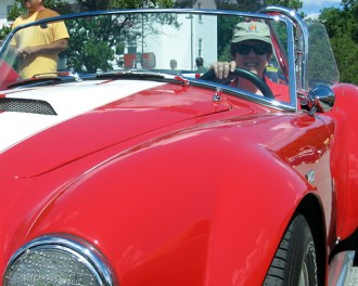 me in the driver seat of a beautiful red Shelby Cobra convertible