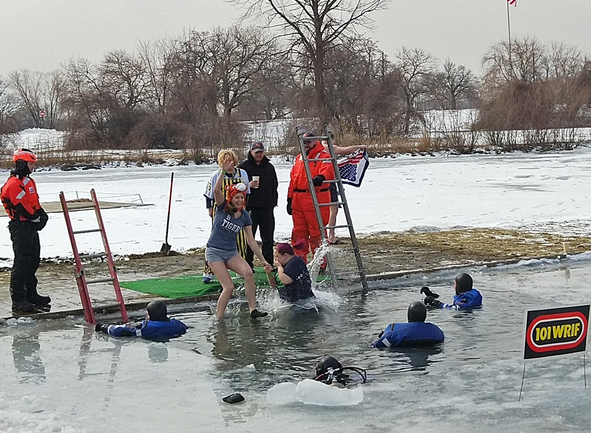 woman midway in air as she jumps into the icy water of the Detroit River as Detroit Police and U.S. Coast Guard Ice Rescue team members wait in water, ready to help.