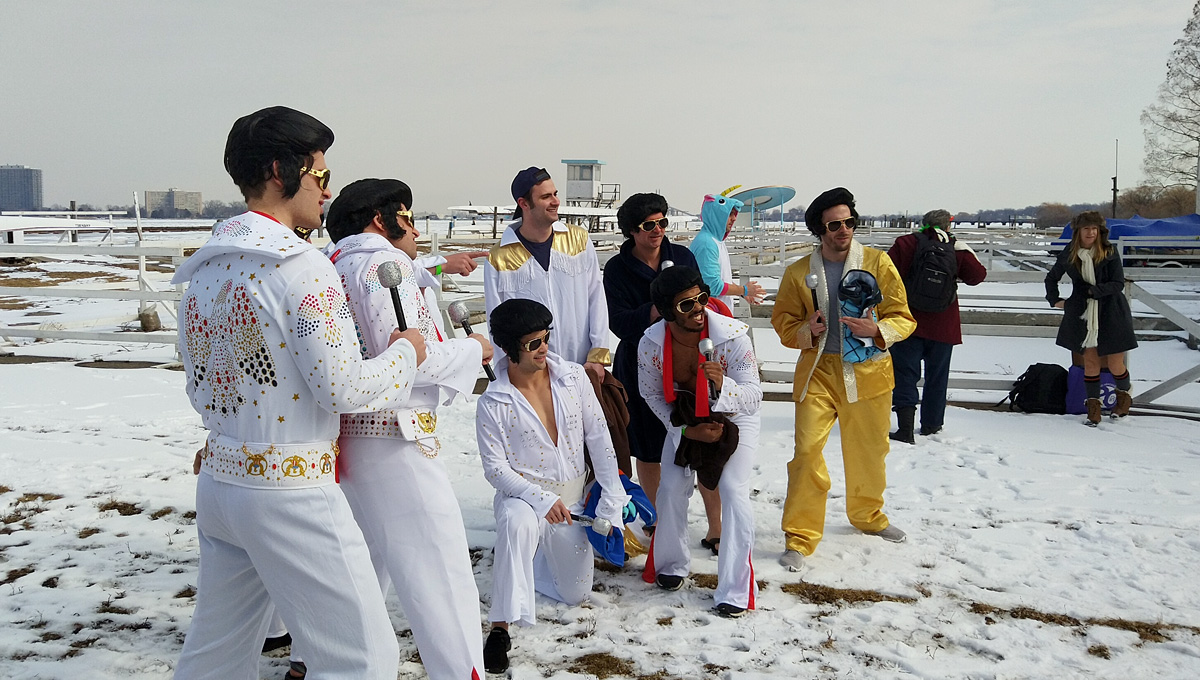group of Elvis impersonators wearing sunglasses, 70's white jumpsuits, with slicked back black wigs.