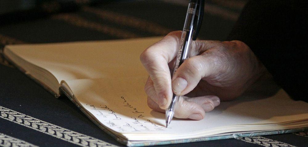 man writing a handwritten note in a journal