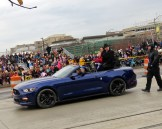 Parade Grand Marshall Tim Allen riding in a blue Mustang with his family in the parade