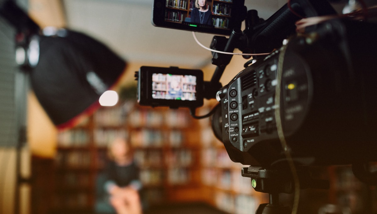 video camera setup with lights on woman seated in chair in front of wall-to-wall bookcase.