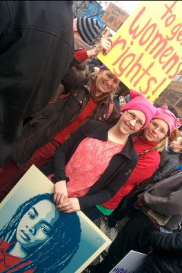 Pink pussy hats on two young women with a poster, their mom holds a yellow Women's Rights sign behind them