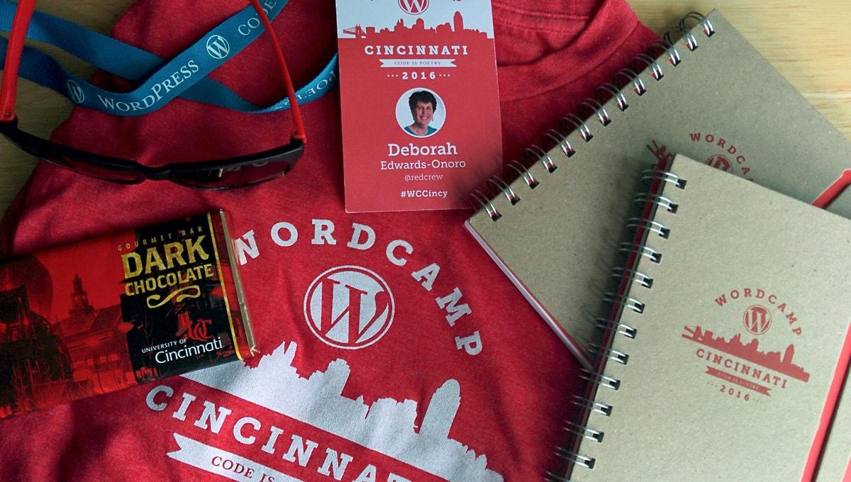 WordCamp Cincinnati red t-shirt, nametag, notebooks, and chocolate bar
