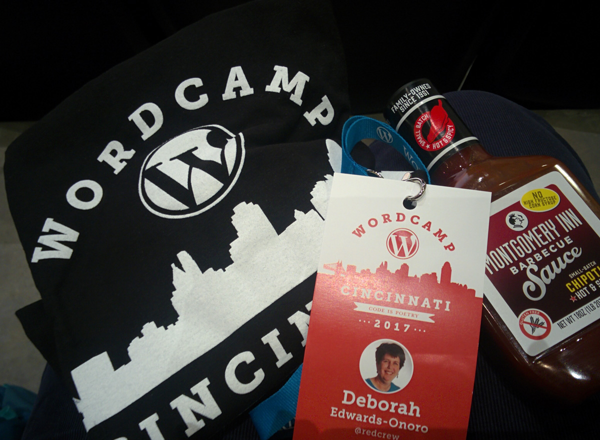 black-WordCamp Cincinnati t-shirt, nametag, and bottle of Montgomery Inn barbecue sauce