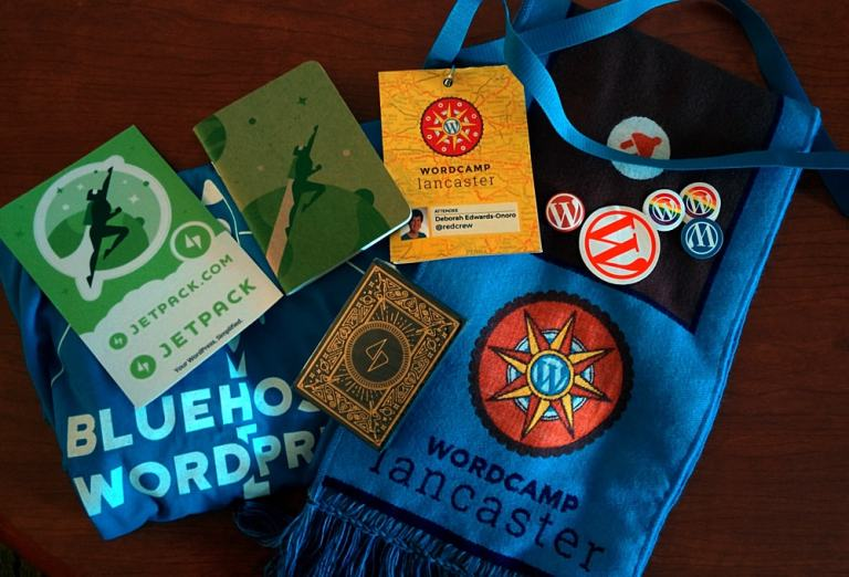 WordCamp Lancaster 2016 scarf, nametag, WordPress stickers, BlueHost t-shirt, and Jetpack cards/notebook