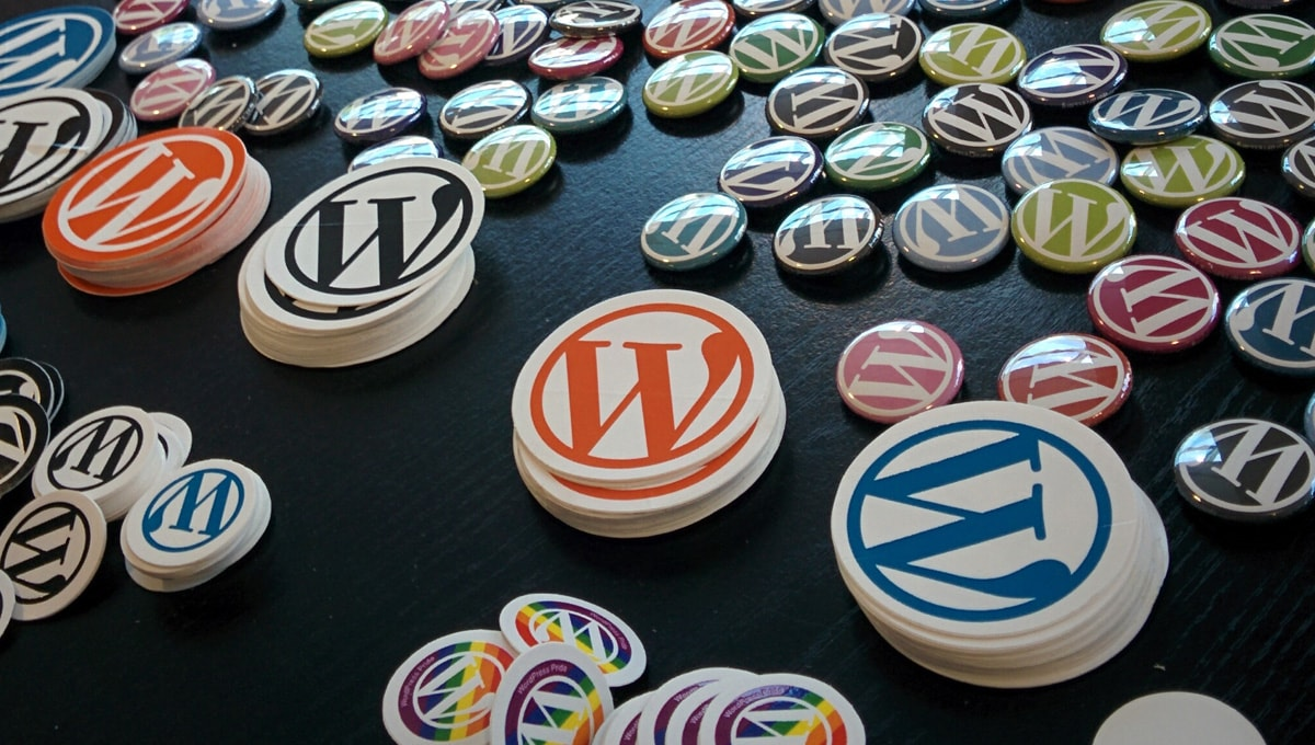 colorful red and blue WordPress stickers strewn across a black table.