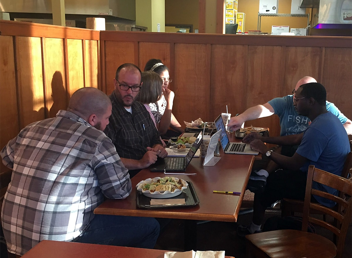 five meetup members gather around tables discussing WordPress issues as experts answer WordPress questions