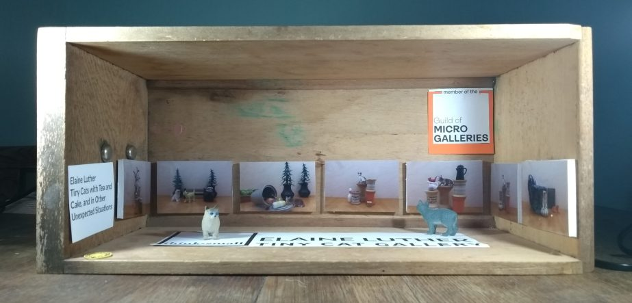 Tiny gallery filled with cats and made inside old dresser drawer